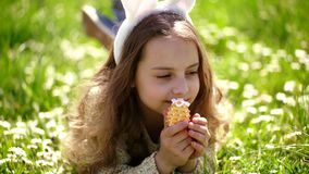 Child with cute bunny ears lying at meadow. Little girl hunting for Easter egg in spring garden on Easter day. Traditional celebration. Easter feast concept stock video