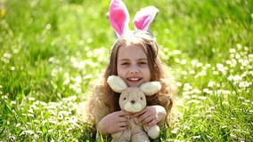 Child with cute bunny ears lying at meadow. Little girl play in spring garden on Easter day, traditional celebration. Easter feast concept. Cute child lay on stock video