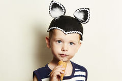 Child. cute kid boy eating ice cream in studio.masquerade Royalty Free Stock Photos