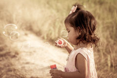 Child cute little girl blowing a soap bubbles in the meadow Stock Photos