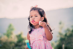 Child cute little girl blowing a soap bubbles in the park Stock Photo