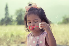 Child cute little girl blowing a soap bubbles in the park Royalty Free Stock Photos