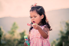 Child cute little girl blowing a soap bubbles in the park Royalty Free Stock Images