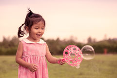 Child cute little girl having fun to play with her bubbles toy Stock Images