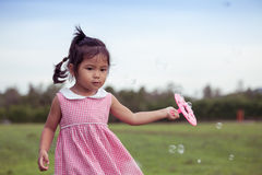 Child cute little girl having fun to play with her bubbles toy Royalty Free Stock Photography