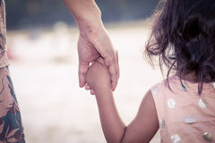 Child cute little girl and mother holding hand together. With love in vintage color filter Stock Image