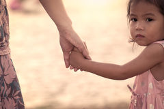 Child cute little girl and mother holding hand together. With love in vintage color filter Stock Photos