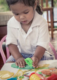 Child cute little girl playing with clay, play doh Royalty Free Stock Image