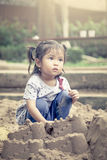 Child cute little girl playing with sand in playground Stock Photography