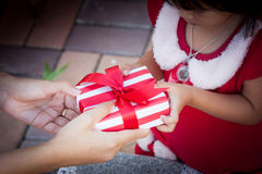 Child cute little girl receiving christmas present from woman Stock Photography