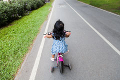 Child cute little girl riding bike. In park Royalty Free Stock Image