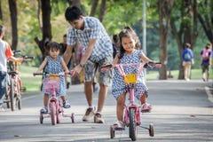 Child cute little girl riding bike in park Stock Photo