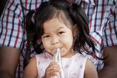 Child cute little girl is sitting on her father and drinking Stock Image