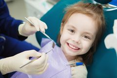 Child with cute smile sits at dentist chair with napkin. On chest and doctor in sterile rubber gloves trys to start examination with special medical instruments royalty free stock photo