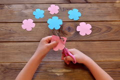 Child cuts a flower of paper. Child holds paper and scissors in his hands. Paper flowers set on a wooden table Stock Photography