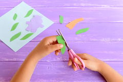 Child cuts a leaf from green paper. Kid holds scissors in his hands. Details to create a card. Child doing crafts from paper Royalty Free Stock Photo