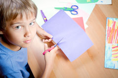 Child cutting colored paper with scissors at the table Stock Images