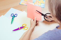 Child cutting colored paper with scissors at the table Royalty Free Stock Photos