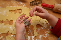 Child cutting out cookies. Christmas baking with kids, child's hands while cutting out the cookies Stock Photography