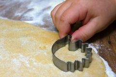 Child cutting out cookies. Christmas baking with kids, child's hands while cutting out the cookies Royalty Free Stock Image
