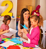 Child cutting paper in class. Development social origami lerning school. Royalty Free Stock Images