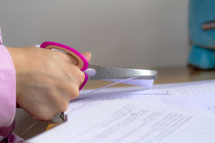 Child cutting paper with scissors royalty free stock photo