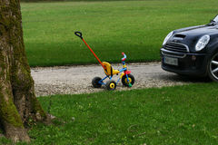 Child cycle. Small coloured child bike facing a black car on a green lawn Royalty Free Stock Photography