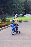Child cycling. Child in blue helmet riding a bicycle Royalty Free Stock Photography