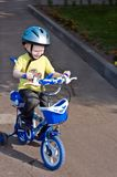 Child cycling. Child in blue helmet riding a bicycle Stock Image