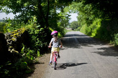 Child cycling a bike. On countryside road Royalty Free Stock Image