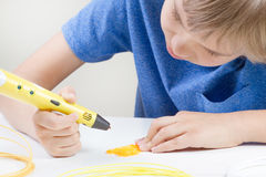 Child with 3d pen. Creative, technology, leisure, education concept. Schoolboy with 3d printing drawing pen. Creative, leisure, technology education concept Stock Image
