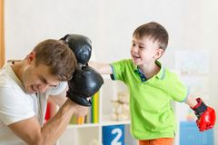 Child and dad play boxing. Kid and dad play boxing in children room royalty free stock photos