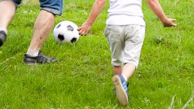 A child with a dad playing football with the ball on the green grass. Legs of a man and a boy with a ball. stock video footage