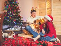 Girl with a dad playing the guitar and singing near christmas tr Stock Photography
