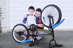 Child and dad repairing broken bicycle Stock Image