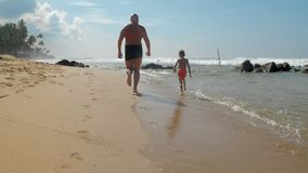 Child with daddy run in coastline against sky slow motion
