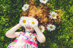 Child with daisy eyes lying on green grass. Stock Photography