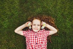 Child with daisy on green grass in a summer park. Royalty Free Stock Image