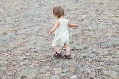 Child dancing outdoors. Little baby girl walking away. Running away little baby girl in steppe. Big landscape environment. Loneliness concept. Travel in Middle stock image