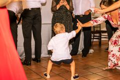 Child dancing with several adults in the celebration of a wedding, encouraging people. Photography made in Madrid, Spain stock images