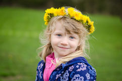 Child with dandelion chain portrait. Beautiful blond girl with yellow dandelion chain over head Stock Images