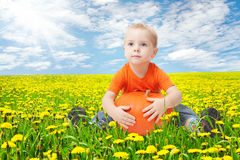 Child in dandelion flowers field, holding pumpkin. Sunny spring day Royalty Free Stock Photography