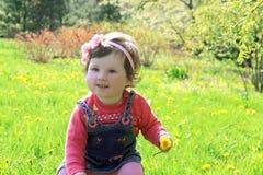 Child among dandelion lawn Stock Photography