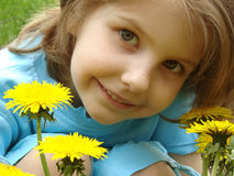Child with dandelions. Little pretty smiling girl outdoor portrait with dandelions Stock Photography