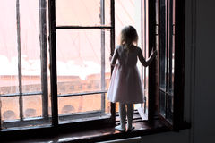 The child is in danger. The girl in the dress is standing on the windowsill Stock Photography