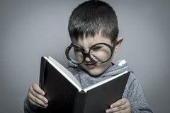 Child, dark-haired young student reading a funny book, reading a Stock Photo