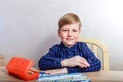Child in a dark shirt sitting at a Desk. Diligent child in a dark shirt sitting at a Desk royalty free stock photography