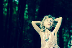 Child in dark woods Stock Photo