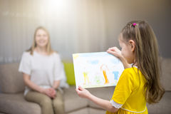 Child daughter congratulates mom and gives her painting. Mum and girl smiling and hugging. Family holiday and happiness. Stock Photos