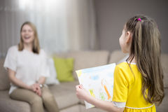 Child daughter congratulates mom and gives her painting. Mum and girl smiling and hugging. Family holiday and happiness. Royalty Free Stock Photography